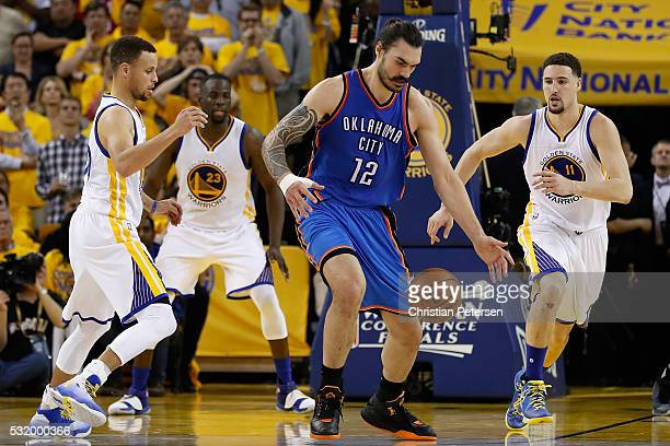 Steven Adams of the Oklahoma City Thunder attempts to control a loose ball against Stephen Curry and Klay Thompson of the Golden State Warriors...