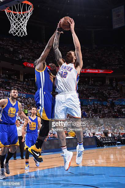 Steven Adams of the Oklahoma City Thunder drives to the basket while guarded by Draymond Green of the Golden State Warriors in Game Four of the...