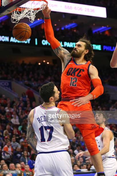 Steven Adams of the Oklahoma City Thunder dunks over JJ Redick of the Philadelphia 76ers during a game at Wells Fargo Center on January 19 2019 in...