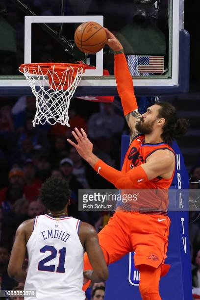 Steven Adams of the Oklahoma City Thunder dunks over Joel Embiid of the Philadelphia 76ers during the first half of a game at Wells Fargo Center on...