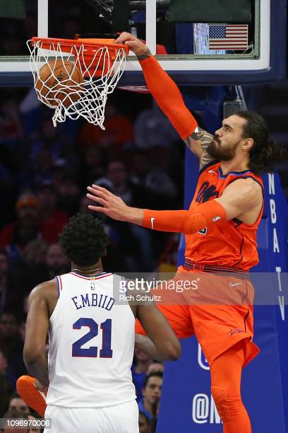Steven Adams of the Oklahoma City Thunder dunks over Joel Embiid the Philadelphia 76ers during a game at Wells Fargo Center on January 19 2019 in...