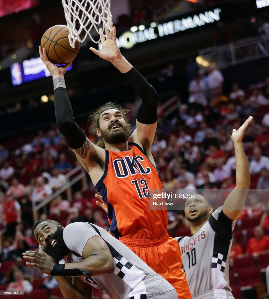 Steven Adams #12 of the Oklahoma City Thunder goes up between James Harden #13 of the Houston Rockets and Eric Gordon #10 for a layup at Toyota Center on March 26, 2017 in Houston, Texas.