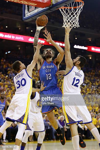 Steven Adams of the Oklahoma City Thunder goes up for a shot against Stephen Curry and Andrew Bogut of the Golden State Warriors in Game Seven of the...