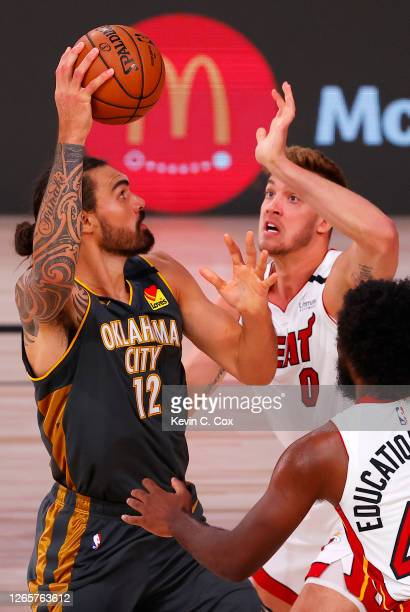 Steven Adams of the Oklahoma City Thunder grabs a rebound against Meyers Leonard and Solomon Hill of the Miami Heat during the third quarter at Visa...