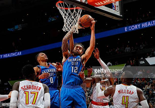 Steven Adams of the Oklahoma City Thunder grabs a rebound against Dennis Schroder Kent Bazemore and Paul Millsap of the Atlanta Hawks at Philips...