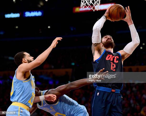Steven Adams of the Oklahoma City Thunder grabs a rebound in front of Tyler Ennis and Julius Randle of the Los Angeles Lakers during a 13396 Thunder...