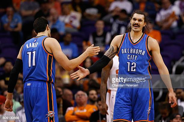 Steven Adams of the Oklahoma City Thunder highfives Enes Kanter after scoring against the Phoenix Suns during the second half of the NBA game at...