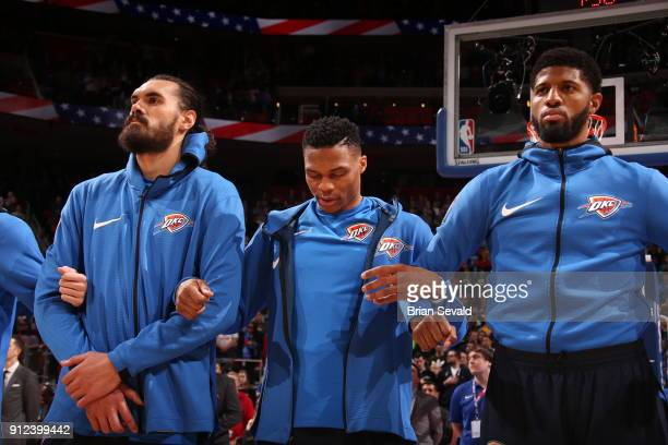 Steven Adams Russell Westbrook and Paul George look on during the national anthem prior to the game against the Detroit Pistons on January 27 2018 at...