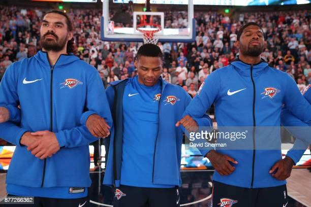 Steven Adams Russell Westbrook and Paul George of the Oklahoma City Thunder stands for the National Anthem before the game against the Utah Jazz on...
