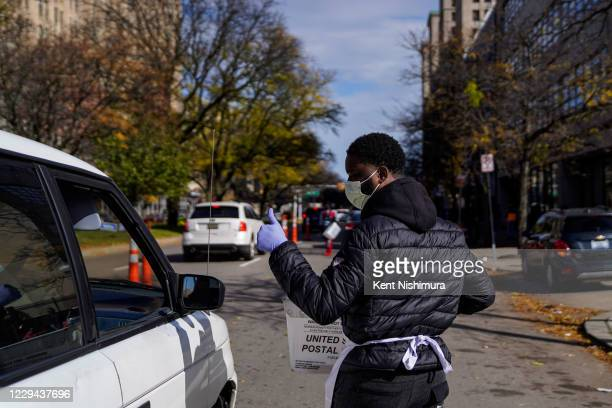 Steven Addo of Detroit collects ballots from cars lining up as voters drop off their ballots or vote in person at the City of Detroit Dept. Of...
