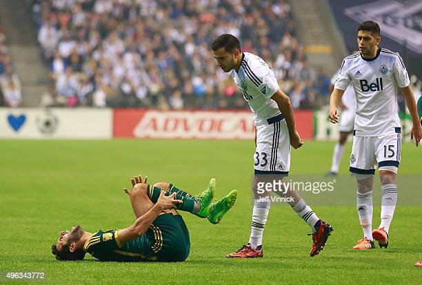 Steven Beitashour and Matias Laba of the Vancouver Whitecaps FC look on as Diego Valeri of the Portland Timbers writhes in pain on the turf during...