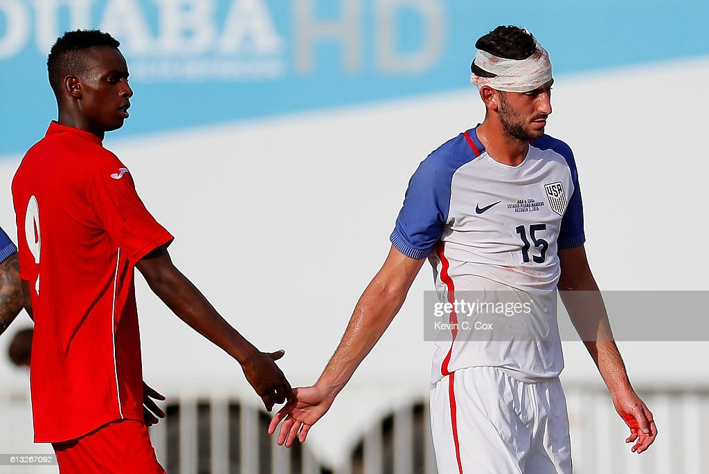 Steven Birnbaum #15 of the United States exits the pitch after a collision as Maykel Reyes Ascuy #9 of Cuba walks over to check on him at Estadio Pedro Marrero on October 7, 2016 in Havana, Cuba.