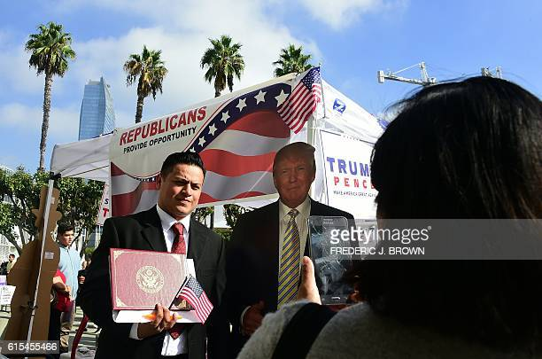 Steven Damin poses beside a carboard cutout of Republican presidential nominee Donald Trump with his certificate of naturalization as volunteers and...
