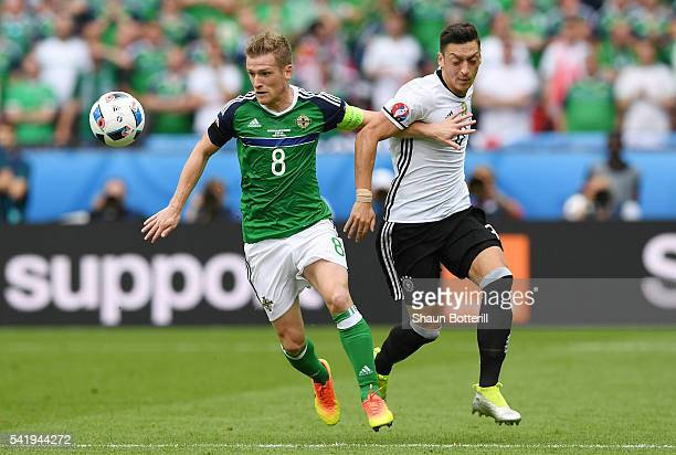 Steven Davis of Northern Ireland and Mesut Oezil of Germany compete for the ball during the UEFA EURO 2016 Group C match between Northern Ireland and...