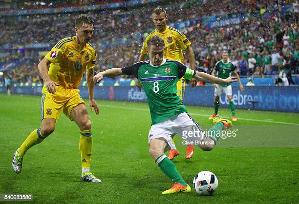 Steven Davis of Northern Ireland and Serhiy Sydorchuk of Ukraine compete for the ball during the UEFA EURO 2016 Group C match between Ukraine and...