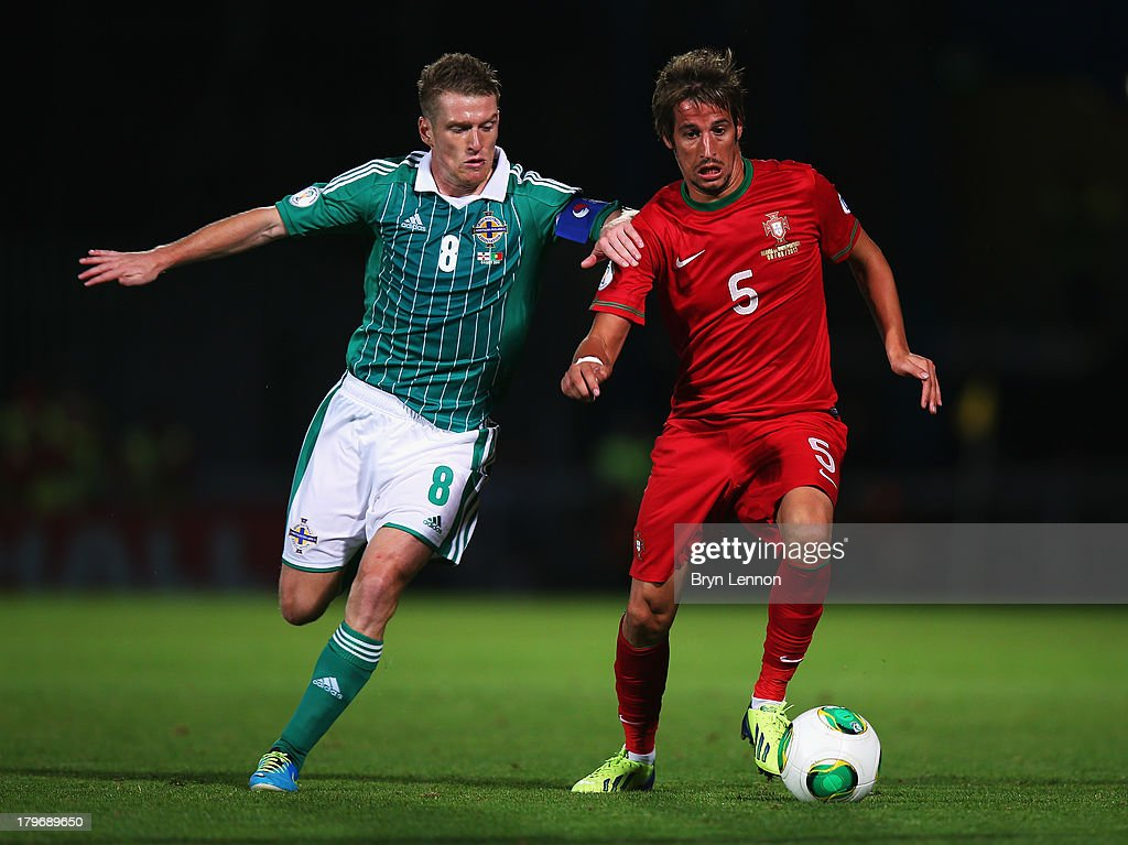 Steven Davis of Northern ireland is tackled by Fabio Coentrao of Portugal during the FIFA 2014 World Cup Qualifying Group F match between Northern Ireland and Portugal at Windsor Park on September 6, 2013 in Belfast, Northern Ireland.