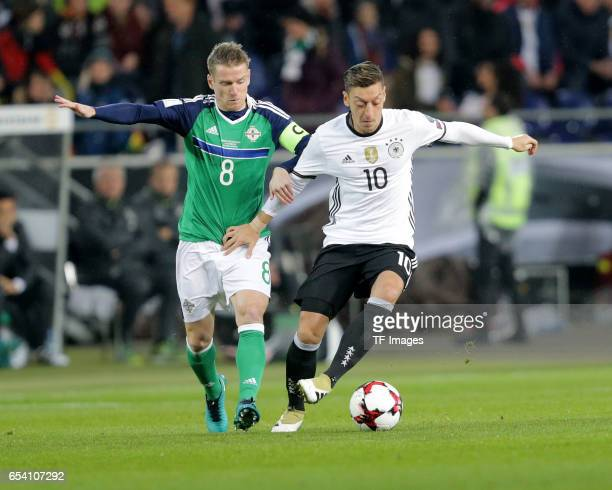 Steven Davis of Northern Ireland Mesut Özil of Germany battle for the balll during the FIFA 2018 World Cup Qualifier between Germany and Northern...