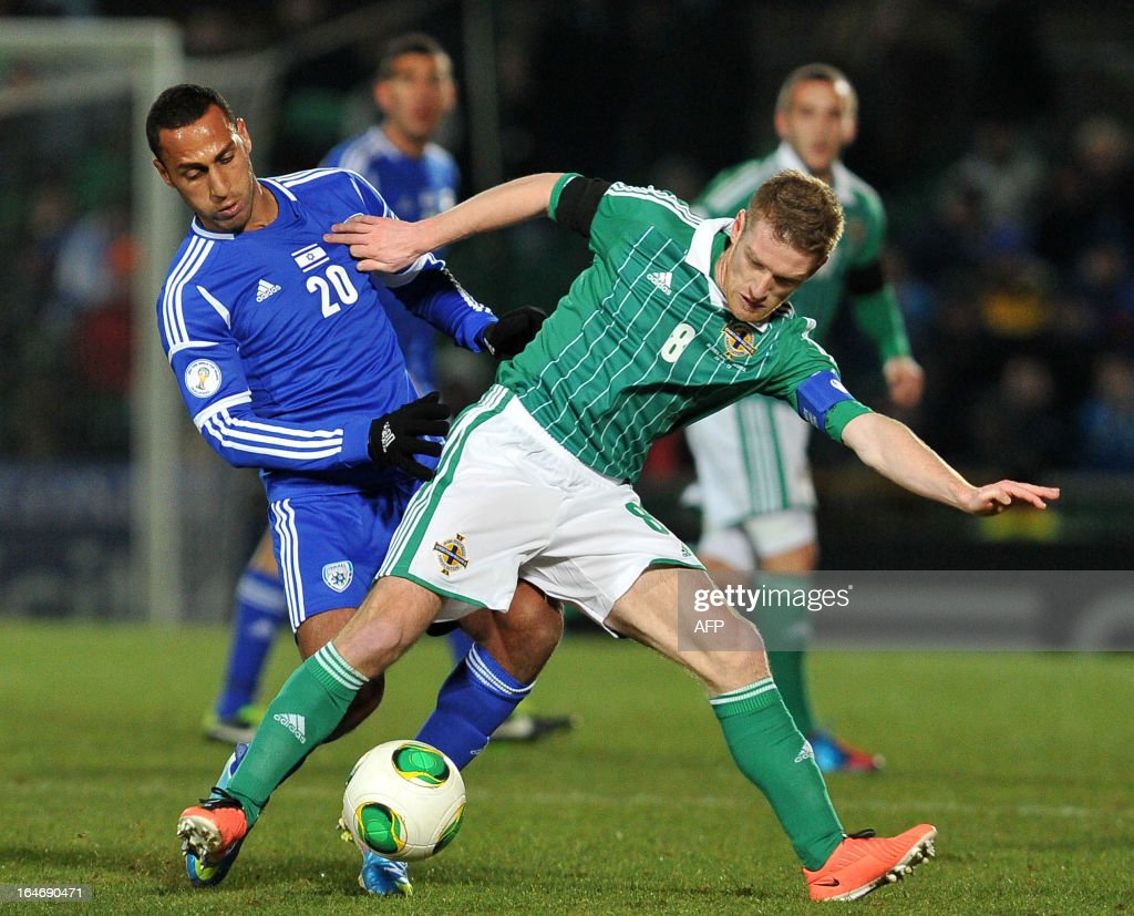Steven Davis of Northern Ireland (R) vies with Maharan Radi of Israel (L) during the FIFA 2014 World Cup qualifying football match between Northern Ireland and Israel at Windsor Park in Belfast, Northern Ireland on March 26, 2013. AFP PHOTO/MICHAEL COOPER