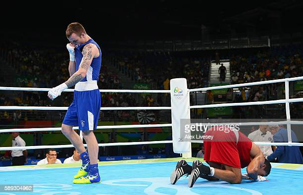 Steven Donnelly of Ireland looks dejected as Mohammed Rabii of Morocco kisses the canvas in victory after the Men's Welterweight Quarter Final bout...