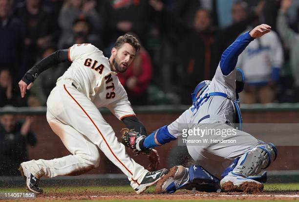 Steven Duggar of the San Francisco Giants scores the winning run sliding past the tag of Russell Martin of the Los Angeles Dodgers in the bottom of...