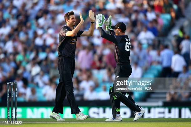 Steven Finn of the Manchester Originals celebrates taking a wicket with team mate Jos Buttler during The Hundred match between Oval Invincibles Men...