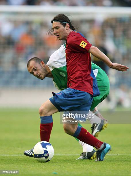 Steven Fletcher of Hibernian FC and Lionel Messi of FC Barcelona