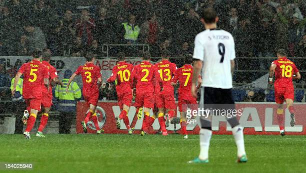 Steven Fletcher of Scotland looks on as the Wales team celebrate their late winning goal of the 2014 World Cup qualifying football match between...