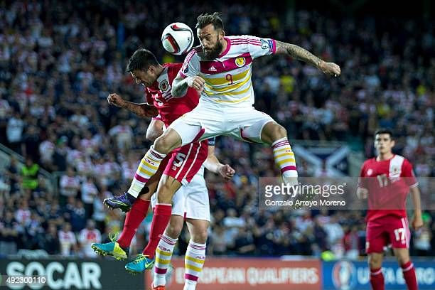Steven Fletcher of Scotland wins the header after Ryan Casciaro of Gibraltar during the UEFA EURO 2016 Qualifying round Group G match between...