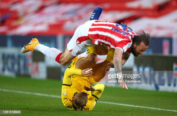 Steven Fletcher of Stoke City is tackled by Michal Helik of Barnsley during the Sky Bet Championship match between Stoke City and Barnsley at Bet365...