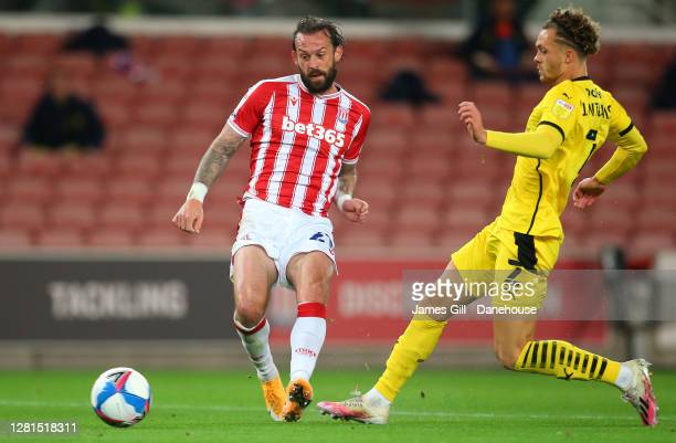 Steven Fletcher of Stoke City shoots under pressure from Jordan Williams of Barnsley during the Sky Bet Championship match between Stoke City and...