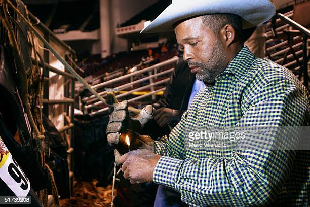 Steven Gabriel of Houston, Texas burns a glove with a sticky rosin upon it to prevent him from coming loose from his saddle during his bronco horse...