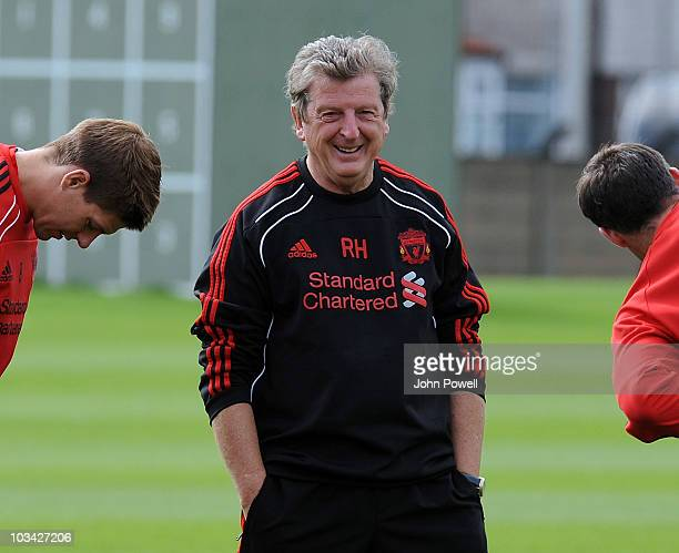 Steven Gerrard and Jamie Carragher of Liverpool limber up either side of manager Roy Hodgson during a training session at Melwood training ground on...
