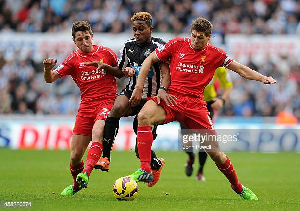 Steven Gerrard and Joe Allen of Liverpool competes with Rolando Aarons of Newcastle United during the Barclays Premier League match between Newcastle...