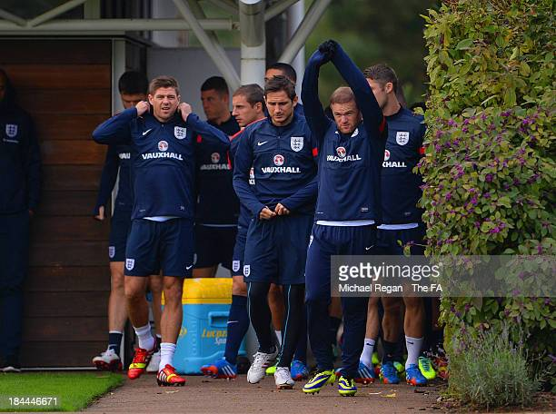 Steven Gerrard, Frank Lampard and Wayne Rooney lead the squad out during the England training session at London Colney on October 14, 2013 in St...