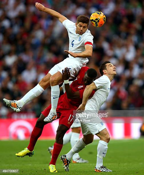 Steven Gerrard of England cloimbs above Luis Advincula of Peru and Leighton Baines of England to win the ball during the international friendly match...