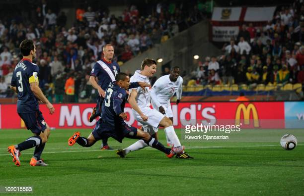 Steven Gerrard of England shoots and scores under pressure from Ricardo Clark of the United States during the 2010 FIFA World Cup South Africa Group...