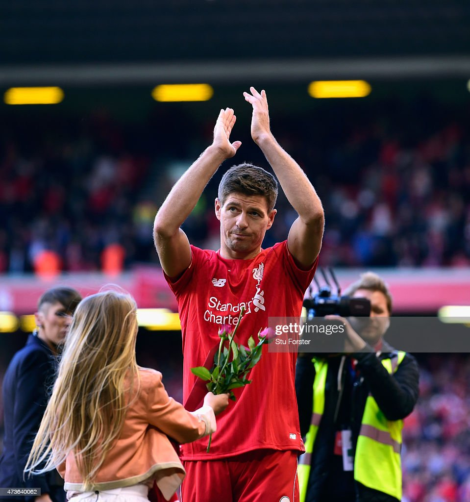 Steven Gerrard of Liverpool applauds the Kop end as his daughter brings him flowers after the Barclays Premier League match betrween Liverpool and Crystal Palace at Anfield on May 16, 2015 in Liverpool, England.