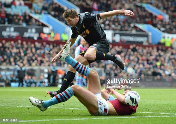 Steven Gerrard of Liverpool battles with Nathan Baker of Aston Villa during the Barclays Premier League match between Aston Villa and Liverpool at...