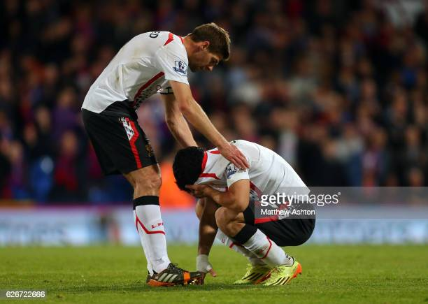 Steven Gerrard of Liverpool comforts a distraught Luis Suarez of Liverpool up from the pitch at the end of the match