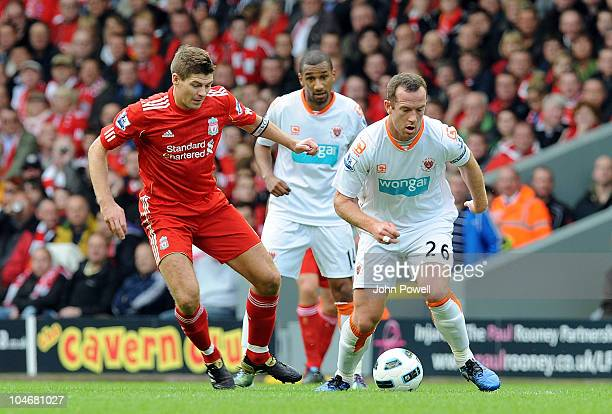 Steven Gerrard of Liverpool goes past Charlie Adam of Blackpool during the Barclays Premier league match between Liverpool and Blackpool at Anfield...