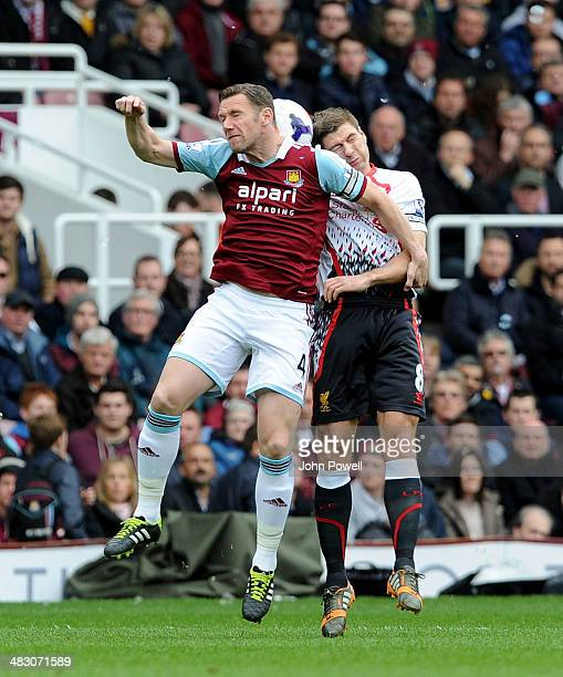 Steven Gerrard of Liverpool goes up with James Tomkins of West Ham United during the Barclays Premier League match between West Ham United and...