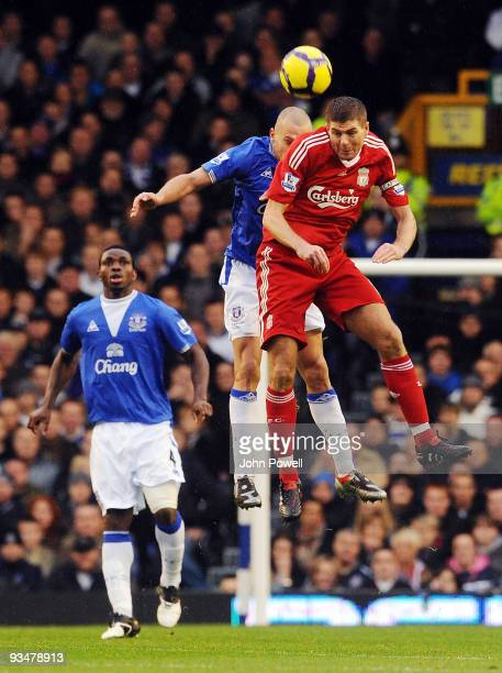 Steven Gerrard of Liverpool goes up with John Heitinga of Everton during the Barclays Premier League match between Everton and Liverpool at Goodison...