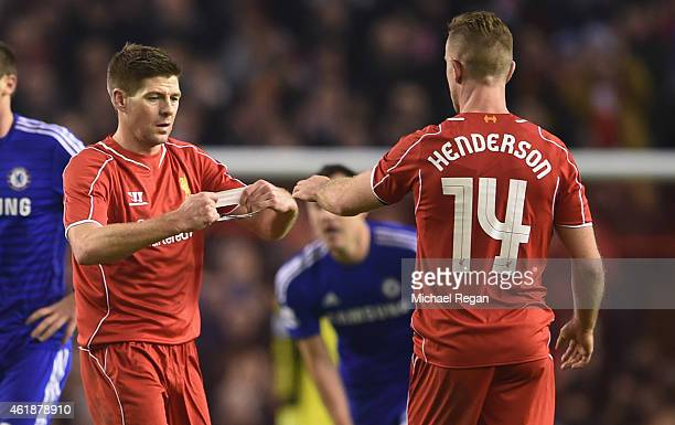 Steven Gerrard of Liverpool hands the Captain's arm band over to Jordan Henderson of Liverpool during the Capital One Cup Semi-Final first leg match...