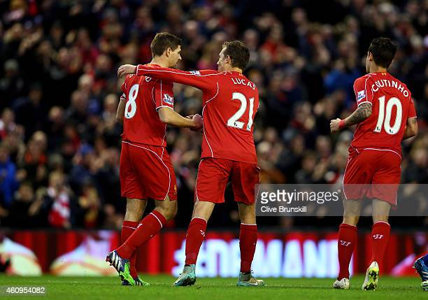 Steven Gerrard of Liverpool is congratulated by teammates Lucas Leiva of Liverpool and Philippe Coutinho of Liverpool after scoring the opening goal...