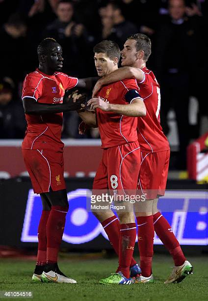 Steven Gerrard of Liverpool is congratulated by teammates Mamadou Sakho and Jordan Henderson after scoring his team's second goal from a free kick...