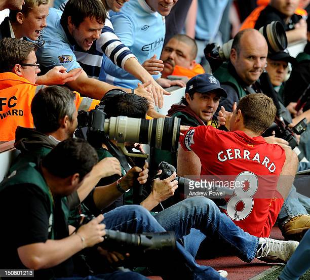 Steven Gerrard of Liverpool is helped up by the Manchester City fans during the Barclays Premier League match between Liverpool and Manchester City...