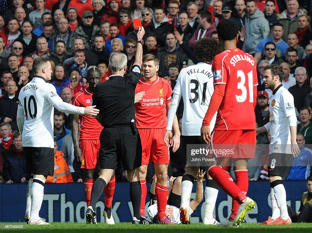 Steven Gerrard of Liverpool is shown the red card by referee Martin Atkinson during the Barclays Premier League match between Liverpool and Manchester United at Anfield on March 22, 2015 in Liverpool, England.