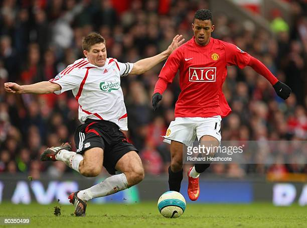 Steven Gerrard of Liverpool tackles Nani of Manchester United during the Barclays Premier League match between Manchester United and Liverpool at Old...