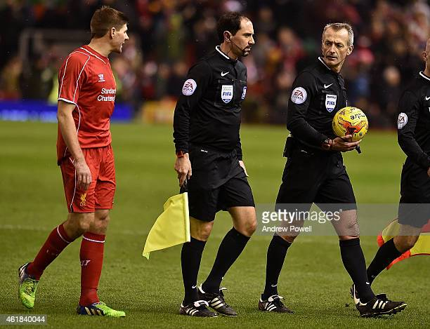 Steven Gerrard of Liverpool talks with referee Martin Atkinson at half time of the Capital One Cup SemiFinal First Leg between Liverpool and Chelsea...