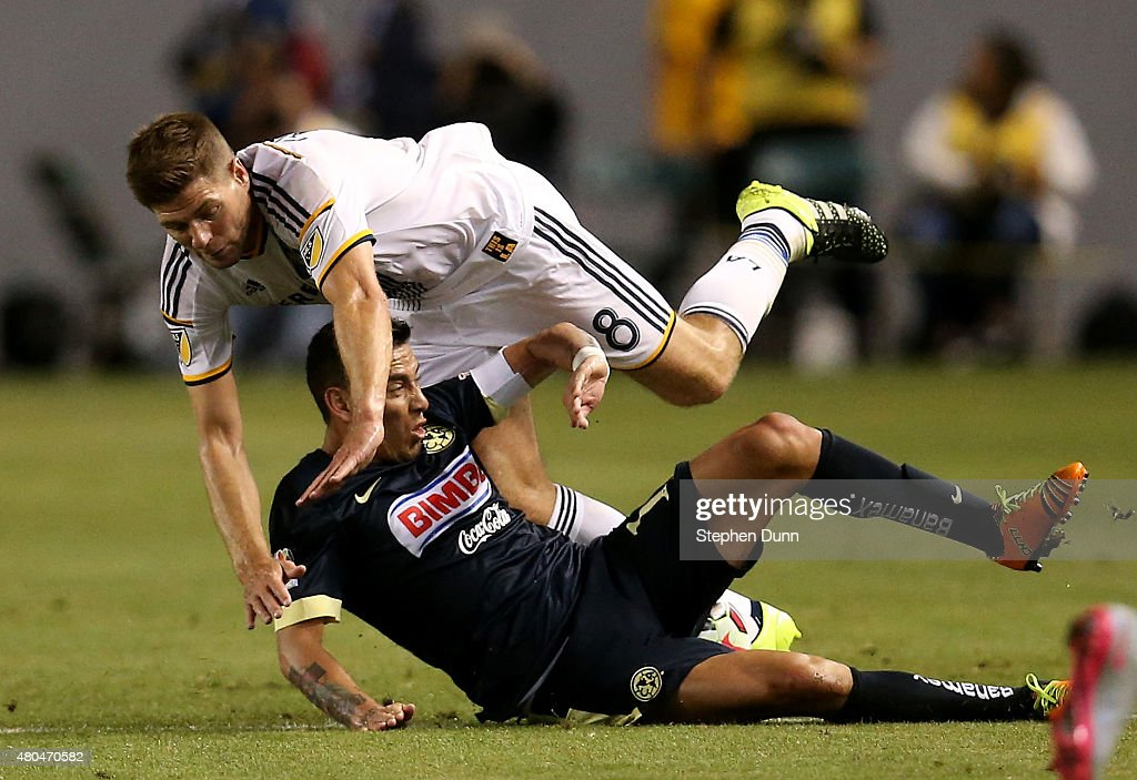 Steven Gerrard #8 of the Los Angeles Galaxy tumbles over Rubens Sambueza #14 of Club America in the International Champions Cup 2015 at StubHub Center on July 11, 2015 in Los Angeles, California.